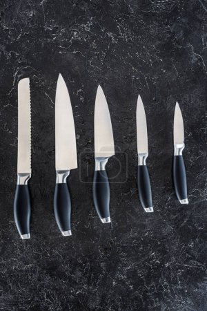 top view of various kitchen knives arranged on black marble surface