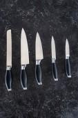 vue de dessus des couteaux de cuisine divers disposées sur la surface du marbre noir
