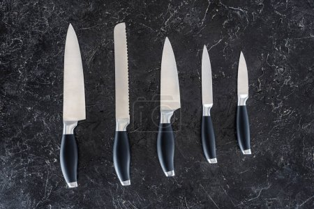 top view of different kitchen knives arranged on black marble surface
