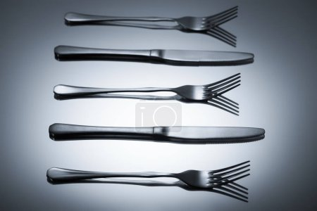 shiny stainless steel forks and knives reflected on grey