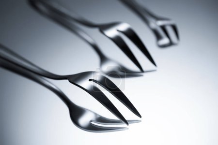 Photo for Close-up view of forks with two tines reflected on grey - Royalty Free Image