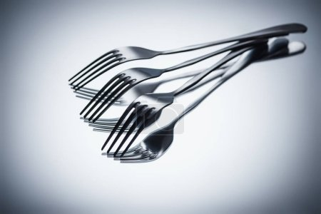 Photo for Close-up view of set of shiny metal forks on grey - Royalty Free Image