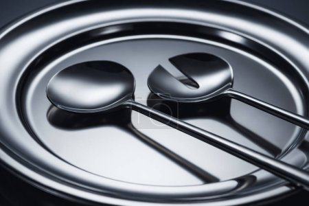 close-up view of shiny ladles on metal tray on grey