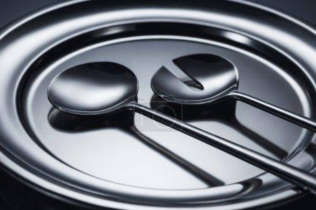 Photo pour Vue rapprochée des louches brillants sur un plateau en métal sur fond gris - image libre de droit