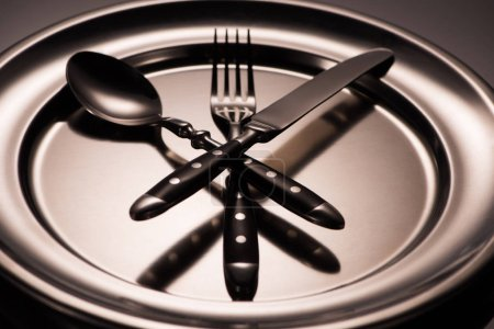 close-up view of cutlery arranged on shiny metal tray on grey