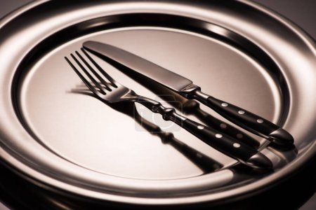 close-up view of fork and knife on shiny metal tray on grey