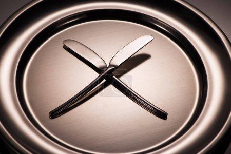 Photo pour Vue rapprochée de deux couteaux sur plaque de métal brillant sur fond gris - image libre de droit