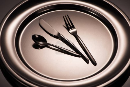 close-up view of spoon, fork and knife on shiny plate on grey