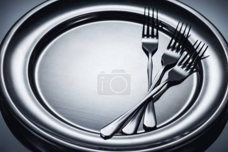 close-up view of three shiny forks on metal tray on grey