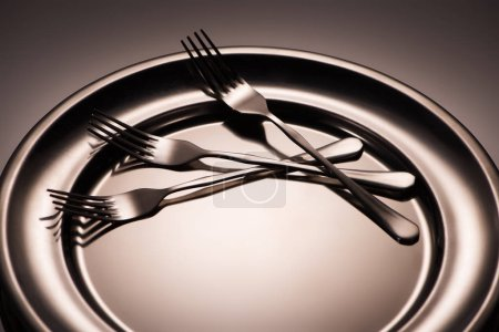 Photo for Close-up view of three forks on shiny metal tray on grey - Royalty Free Image