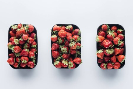 Photo for Top view of row of plastic containers with ripe strawberries on white surface - Royalty Free Image