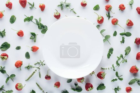 top view of empty plate surrounded with ripe strawberries and mint leaves on white tabletop