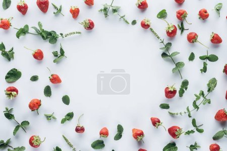 top view of round frame made of ripe strawberries with mint leaves on white tabletop