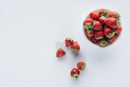 Photo for Top view of bowl of fresh whole strawberries on white surface - Royalty Free Image