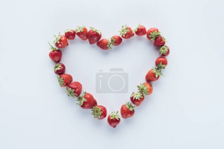 top view of heart shape sign made of fresh strawberries on white surface