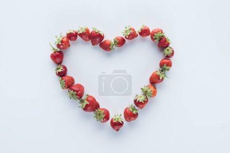 vue de dessus du signe de forme de coeur fait de fraises fraîches sur la surface blanche