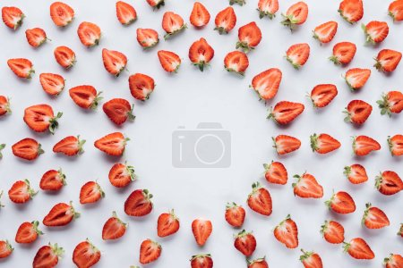 top view of round frame of ripe halved strawberries on white surface