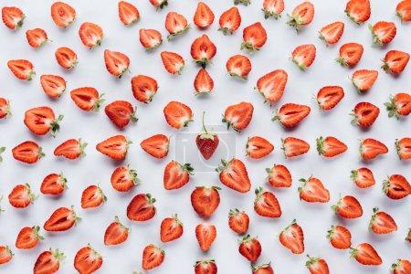 Foto de Vista superior de composición redondo hecho de fresas a la mitad en superficie blanca - Imagen libre de derechos