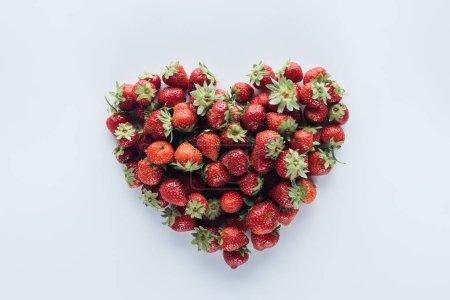 Photo pour Vue de dessus du signe de forme de coeur fait de fraise mûre sur surface blanche - image libre de droit