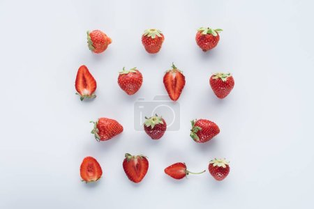 top view of halved and whole strawberries on white surface
