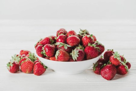 close-up shot of bowl of strawberries on white surface