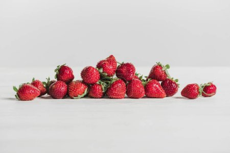 close-up shot of pile of strawberries lying on white