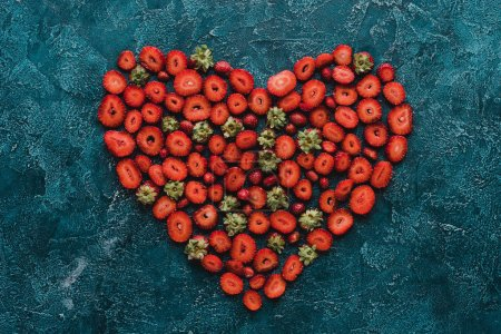 top view of heart sign made of ripe strawberries on blue concrete surface