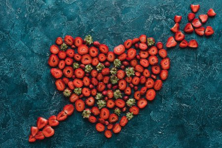 top view of heart pierced with arrow sign made of strawberries on blue concrete surface