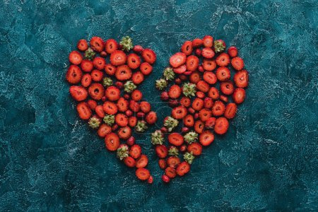 top view of halved heart sign made of ripe strawberries on blue concrete surface
