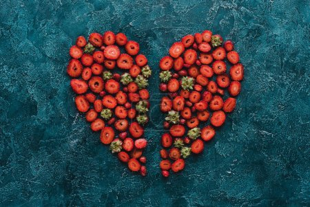 Top view of halved heart sign made of strawberries on blue concrete surface