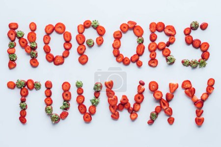 top view of part of alphabet letters made of fresh sliced strawberries on white surface
