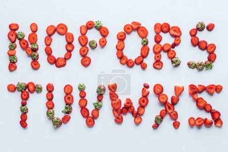 top view of part of alphabet letters made of ripe sliced strawberries on white surface