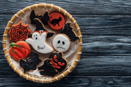 top view of wicker basket with homemade spooky halloween cookies on wooden table