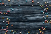 elevated view of arranged colorful delicious candies on wooden background