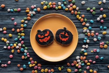 view from above of plate with halloween cookies surrounded by colorful candies on wooden table