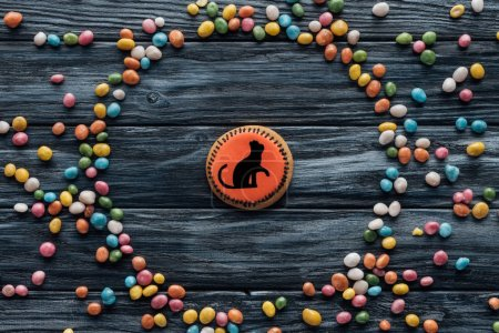 elevated view of composition with homemade halloween cookie surrounded by colorful candies on wooden table