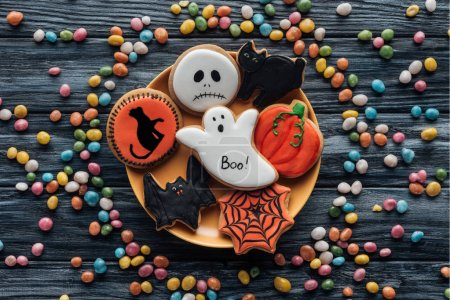 top view of plate with halloween cookies surrounded by colorful candies on wooden table