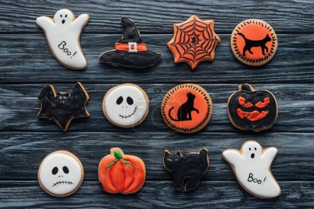 elevated view of composition with sppoky halloween cookies on wooden table