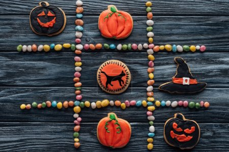 top view of composition from colorful candies and arranged halloween cookies on wooden table