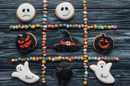 elevated view of composition from colorful candies and arranged halloween cookies on wooden table