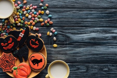 top view of plate with halloween cookies, colorful candies, cups with milk on wooden table