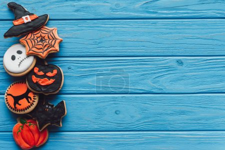top view of spooky homemade halloween cookies placed in row on blue wooden background