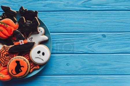 top view of plate with delicious homemade halloween cookies on wooden background