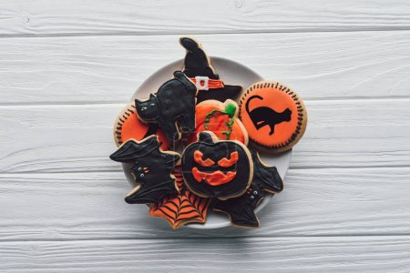 top view of plate homemade halloween cookies on wooden table