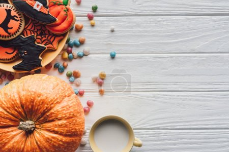 elevated view of pumpkin, plate with halloween cookies, candies and cup with milk on wooden background