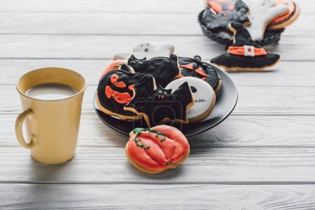 plate with delicious halloween cookies and cup of milk on wooden table