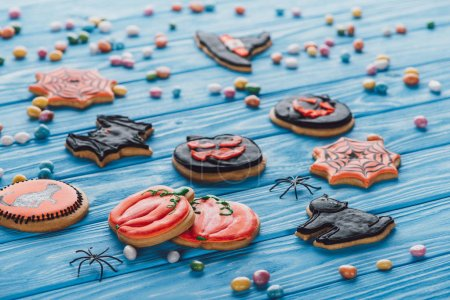 Photo for Colorful candies and homemade halloween cookies on blue wooden table - Royalty Free Image