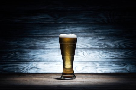 Photo pour Verre de bière savoureuse avec mousse sur table en bois, concept oktoberfest - image libre de droit
