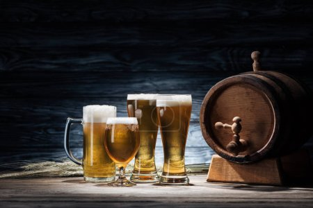 glasses of tasty beer, wheat spikelets and beer barrel on wooden table, oktoberfest concept
