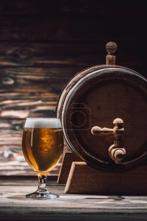 glass of fresh beer and beer barrel on wooden table, oktoberfest concept